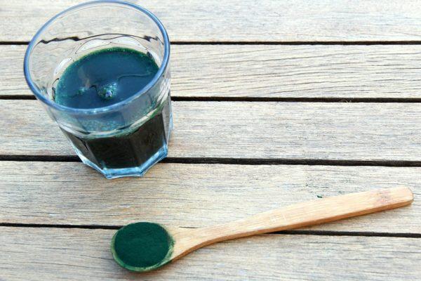 Photo de spiruline dans un verre et une cuillère en bois