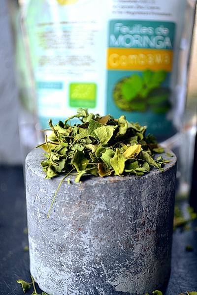 Photo de feuilles de moringa avec du combawa sur fond de sachet d'infusion Dihé